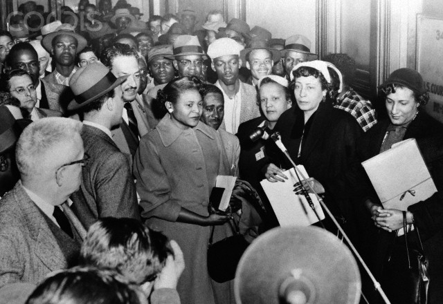 Autherine Lucy (C, no hat) leaves a crowded Federal Court hearing for lunch recess, carrying a Bible. Accompanying her are Thurgood Marshall (striped tie), attorney Arthur Shores (at Miss Lucy's left shoulder), Mrs. Constance Motley (far right), and Mrs. Ruby Hurley, NAACP executive secretary. Miss Lucy's reinstatement was ordered by the court, but she was later expelled from the University on other charges.