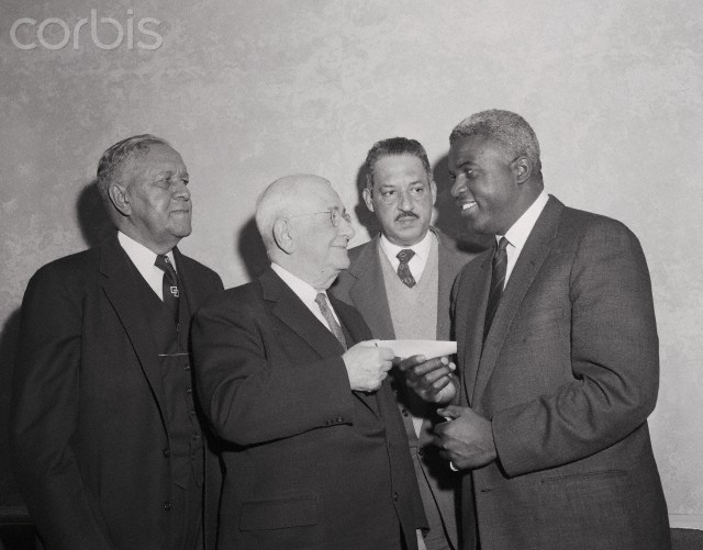 "17 Jan 1957 --- Original caption: Jackie Robinson, who retired from baseball recently to become an executive with Chock Full O'Nuts Corporation, is shown presenting a check for $10,000 on behalf of William Black, president of the corporation, to Arthur B. Spingarn, president of the National Association for the Advancement of Colored People, at a meeting in the Hotel Roosevelt. Left to right: Dr. Channing H. Tobias, Chairman of the Board, NCAAP, Arthur Spingarn, Thurgood Marshall, counsel, and Robinson. The contribution launched NCAAP's ""Fight for Freedom Fund"" drive. The goal is one million dollars a year for the purpose of eliminating racial discrimination and segregation. January 1, 1963, the centennial of Abraham Lincoln's Emancipation Proclamation is the date set to achieve to goal. Robinson is General Chairman of the fund drive for 1957."