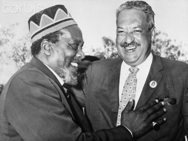 Kenya Premier Jomo Kenyatta (l) shares hearty laugh with U.S. Federal Judge Thurgood Marshall upon the latter's arrival here July 11th. Judge Marshall, former attorney for the National Association for the Advancement of Colored People, is here for a short visit.