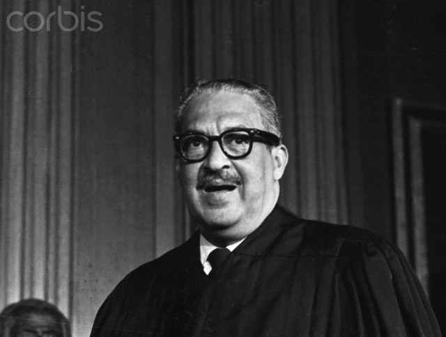 Thurgood Marshall poses in his robes just before taking his seat as the first Negro member of the US Supreme Court today. Marshall, the great grandson of a slave, swore to do equal right to the poor and the rich as he took oath at the opening session of the court.