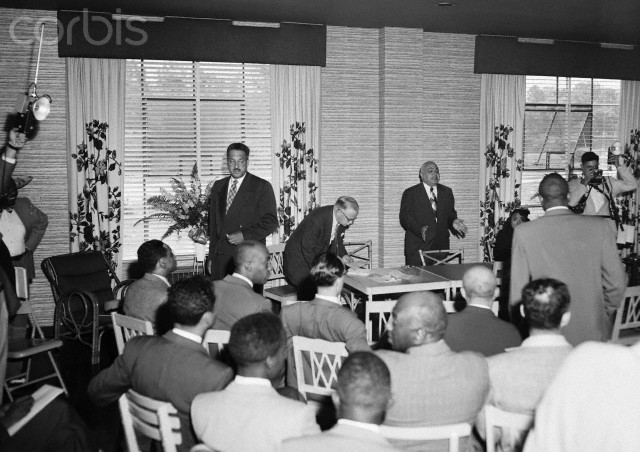 Officials of the National Association for the Advancement of Colored People from 17 states meet in Atlanta, May 22nd, 1954, to plan a course of action in regard to the Supreme Court ruling banning school segregation. Rev. J.M. Hinton addresses the gathering; NAACP Executive Secretary Walter White bends over the table. Thurgood Marshall stands to the left.