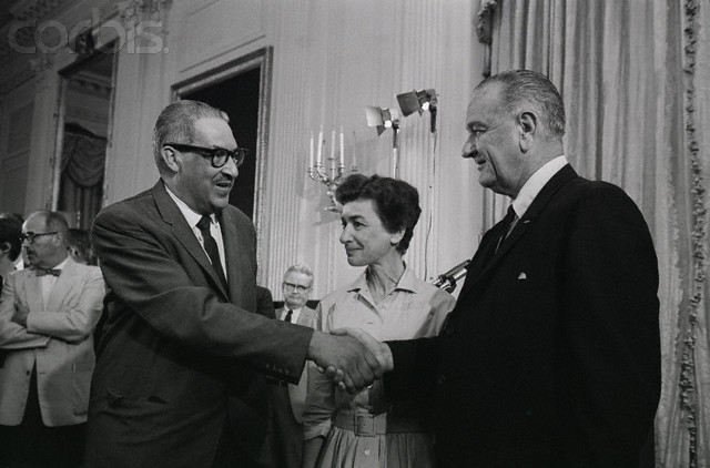 President Johnson congratulates Federal Appeals Judge Thurgood Marshall, a former Negro leader in the civil rights cause, after announcing at his news conference today that he was appointing him to be U.S. Solicitor-General. In the center is Mrs. Penelope Thunberg, Deputy Chief of the International Division of the Economic and Research Area at the CIA, whom he asked to serve as a member of the U.S. Tariff Commission. (ORIGINAL CAPTION)