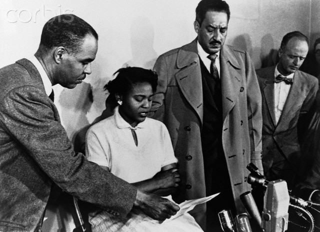 Director of the National Association for the Advancement of Colored People, holds a piece of paper for Autherine Lucy as she speaks at a press conference along with Thurgood Marshall, attorney and Special Counsel for the NAACP Legal Defense and Education Fund. New York, New York.