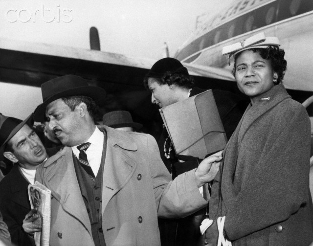 Autherine Lucy (right) comes down a plane ramp at New York's LaGuardia Field March 1 after arriving on a flight from Birmingham. Accompanying her are attorneys Thurgood Marshall and Mrs. Constance Motley. An unidentified reporter (left) approaches Marshall as the trio leaves the plane. Miss Lucy is in New York to rest and undergo a medical checkup. Before her arrival, it was reported that the University of Alabama had expelled her. That action came after a federal judge had ordered her readmitted to classes next Monday despite open-court warnings she might be killed by a mob.