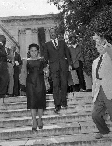 Thurgood Marshall, Chief Counsel for the National Association for the Advancement of Colored People, and his wife, leave the Supreme Court today after the high court's ruling ordering the Little Rock School Board to proceed with integration at Central High School. (Mrs. Marshall has eyes closed)