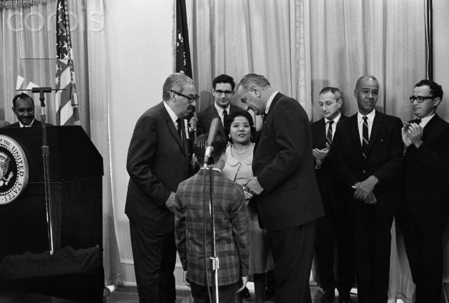 24 Aug 1965, Washington, DC, USA --- Original caption: 8/24/1965-Washington, D.C.: Thurgood Marshall, the first Negro to become U.S. Solicitor General, introduces President Johnson to Mrs. Marshall and their sons, Thurgood, Jr. (back to camera), 9, and John (hidden), 7, after taking his oath in a White House ceremony. In center background is Paul Bender, Assistant to the Solicitor General.