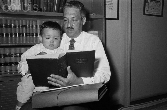"Thurgood Marshall, attorney for the National Association for the Advancement of Colored People, reads ""Political and Civil rights in the United States"" to his son Thurgood, Jr. at home. Marshall announced that the NAACP plans to appeal the ruling by Federal Judge Harry Lemley, suspending integration in Little Rock, Arkansas Central High School for two and half years."