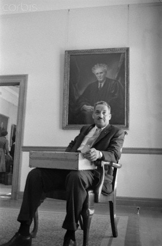 Thurgood Marshall, counsel for the National Association for the Advancement of Colored People, relaxes in the lawyers' lounge today after presenting the NAACP's case to the Supreme Court in the momentous Little Rock school integration case. He is sitting in front of a portrait of the Supreme Court Justice Louis Brandeis, a great liberal.