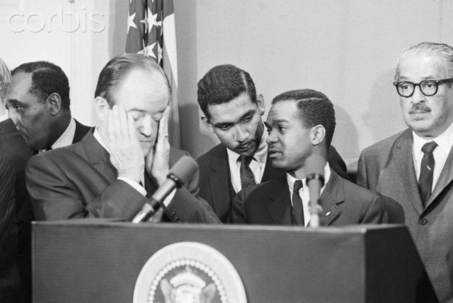 05 Apr 1968, Washington, DC, USA --- Original caption: 4/5/1968-Washington, D.C.: Tension shows on the faces of Vice President Humphrey (L) and Walter E. Fauntroy (R), member of the Washington city council, as they wait at a podium in the White House for President Johnson to make his television speech to the nation in an effort to avoid violence in the wake of the assassination of Dr. Martin Luther King. In the center is Clarence Mitchell III, one of a number of Negro leaders called to the White House meeting. (ORIGINAL CAPTION)